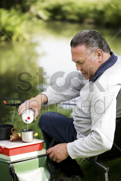 man pouring water from a flask while fishing by the river stock photo
