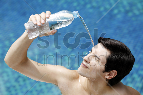 man pouring water on his face stock photo