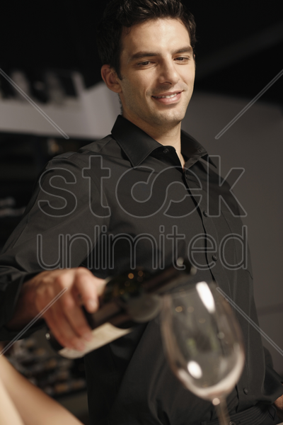 man pouring wine into woman's glass stock photo
