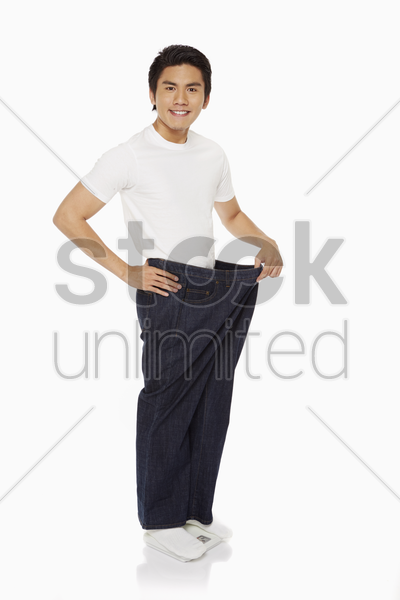 man pulling an oversized jeans stock photo
