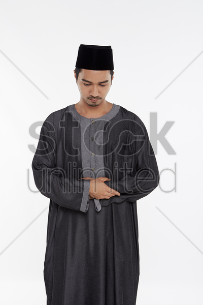 man putting his right hand on top of the left hand, placing it against his chest stock photo