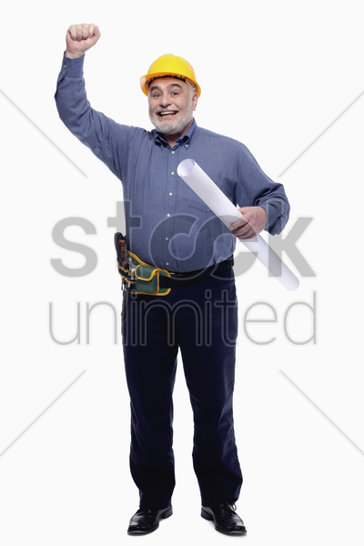 man raising his arm while holding a roll of blueprint stock photo