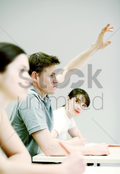 man raising his hand to answer question stock photo