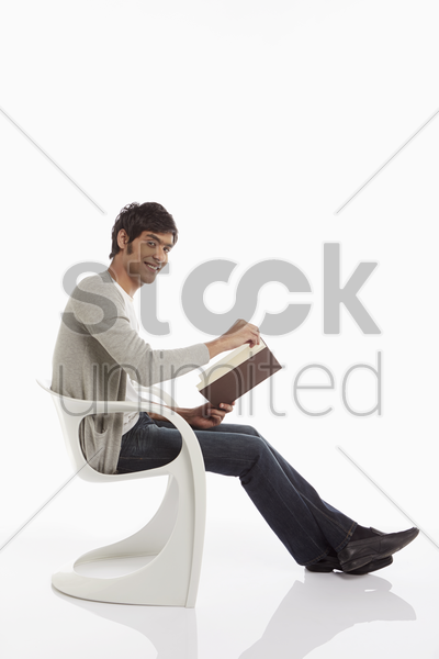 man reading a book while sitting stock photo
