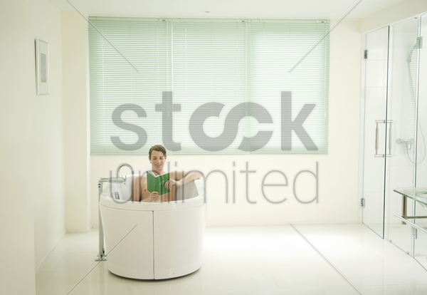 man reading book while sitting in a bathtub stock photo