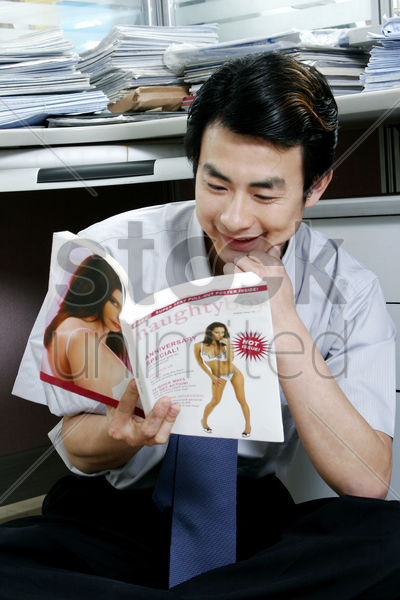 man reading pornographic magazine in the office stock photo