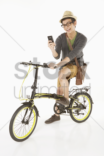 man reading text message while sitting on the bicycle stock photo