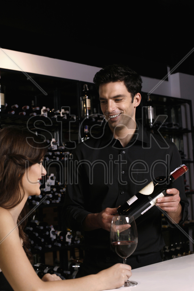man recommending a bottle of wine to woman stock photo