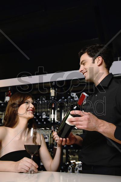 man recommending good wine to woman stock photo