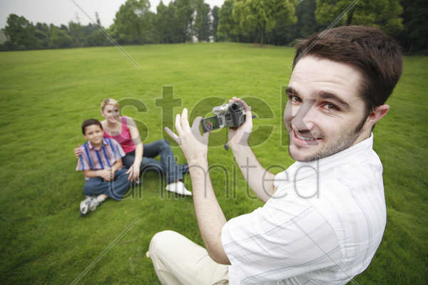 man recording images of boy and girl stock photo