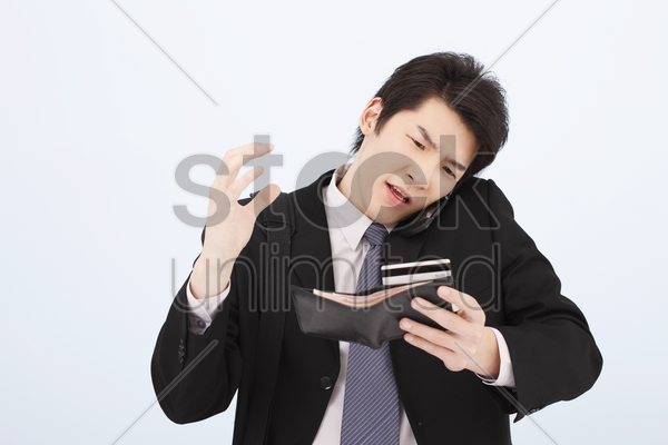 man referring to his credit card while talking on the phone stock photo
