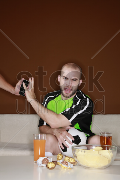 man refusing a phone call when watching football match at home stock photo