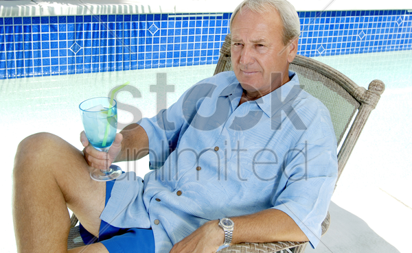 man relaxing by the pool side stock photo