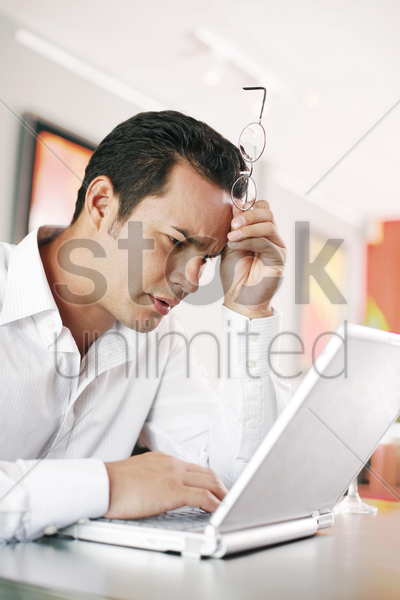 man resting his head while using laptop stock photo