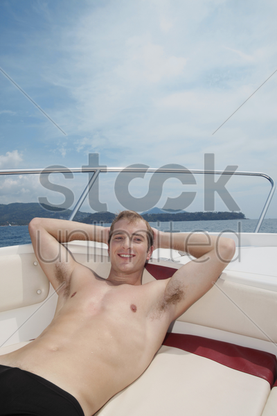 man resting on speedboat stock photo