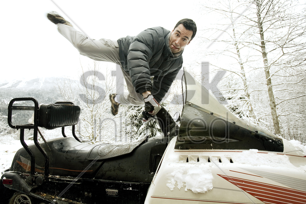 man riding on snowmobile stock photo