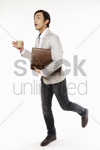 man running while holding briefcase and disposable cup stock photo