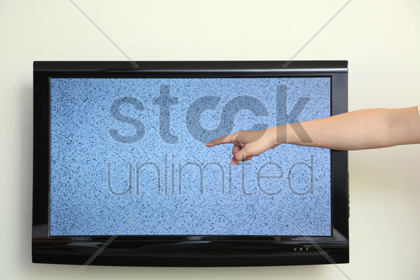 man's hand pointing at ruined television stock photo