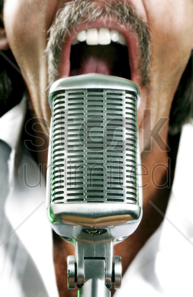 man screaming into a microphone stock photo