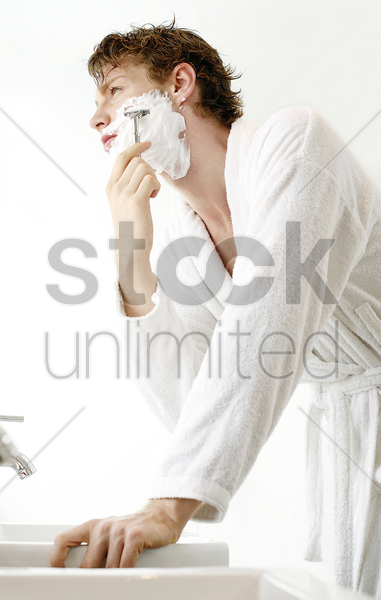 man shaving in the bathroom stock photo