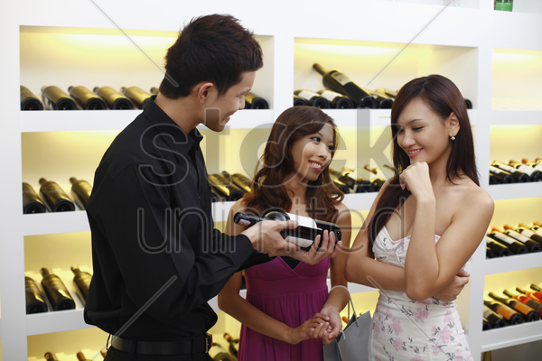 man showing a bottle of red wine to women stock photo