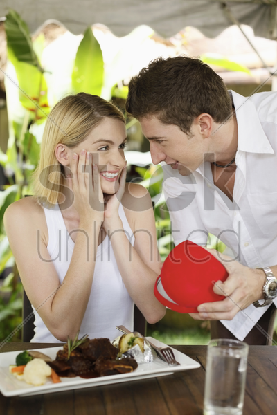 man showing woman a surprise gift stock photo