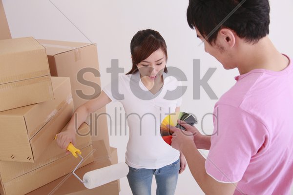 man showing woman color swatch, woman holding a paint roller stock photo