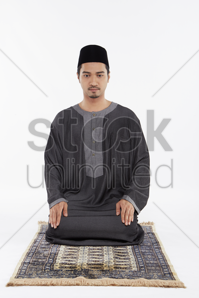 man sitting between the two sujuds stock photo