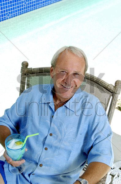 man sitting by the pool side enjoying his drink stock photo