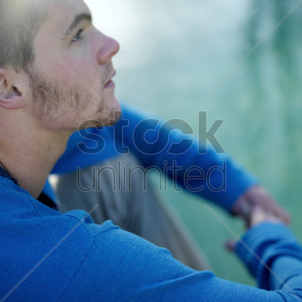 man sitting down daydreaming stock photo