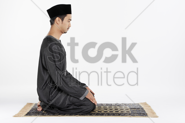 man sitting in between two sujuds stock photo