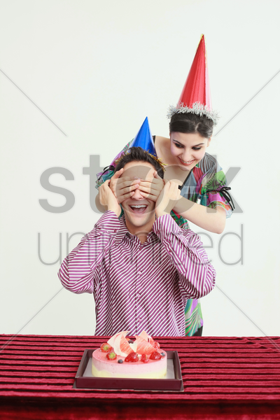 man sitting in front of a cake, woman covering man's eyes with hands stock photo