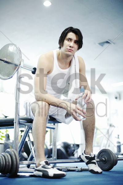 man sitting in gym holding bottled water stock photo