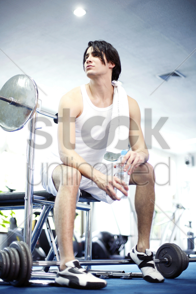 man sitting in the gymnasium holding bottled water stock photo