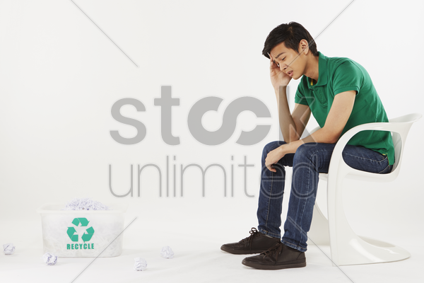 man sitting on a chair, feeling stressed stock photo