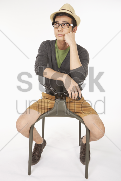 man sitting on a chair, looking sad stock photo