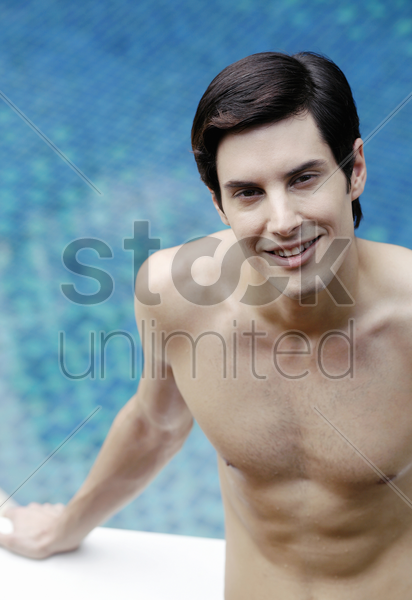 man sitting on massage table by the pool side stock photo