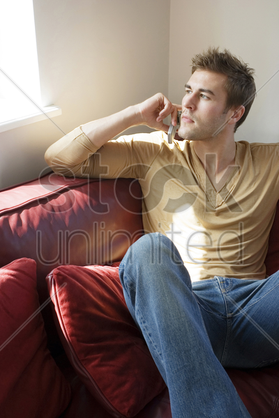 man sitting on the bed talking on the mobile phone stock photo