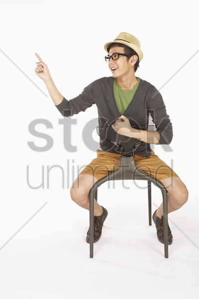 man sitting on the chair and pointing to the right stock photo