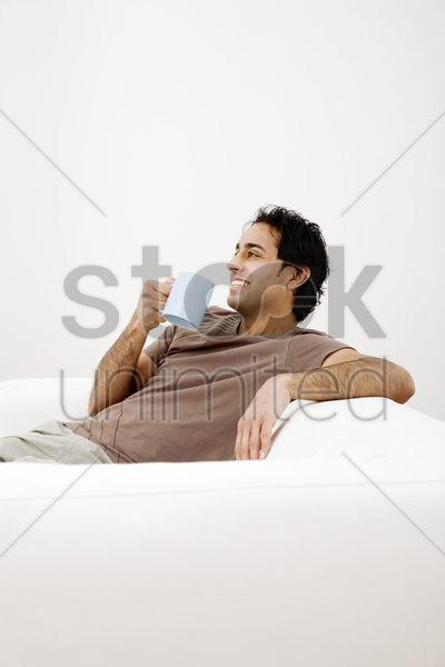 man sitting on the couch drinking coffee stock photo
