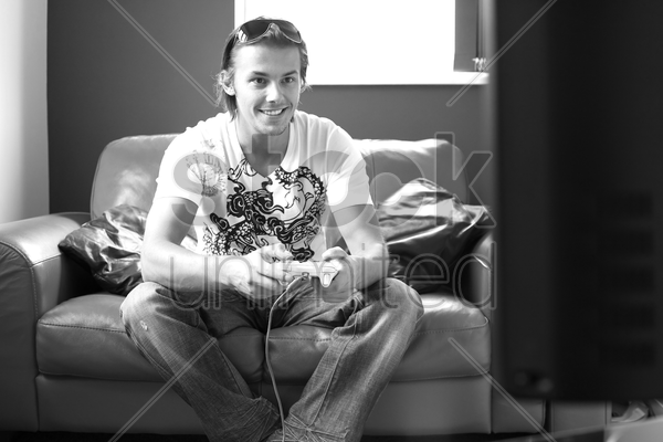 man sitting on the couch playing video game console stock photo