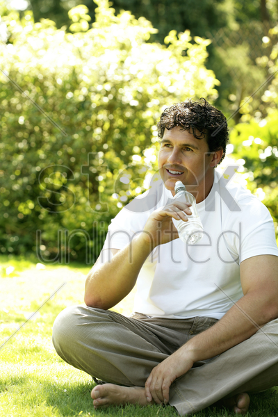 man sitting on the field holding a bottled drinking water stock photo