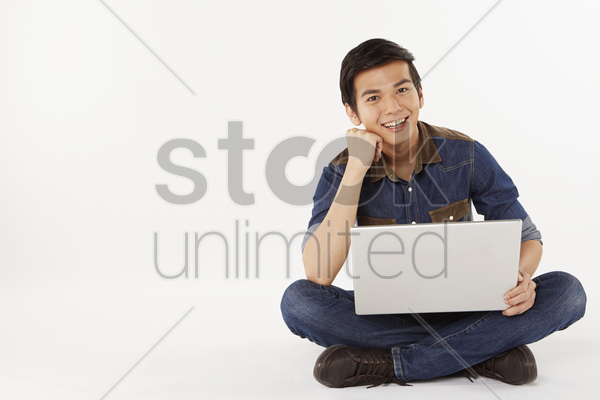 man sitting on the floor, using laptop stock photo