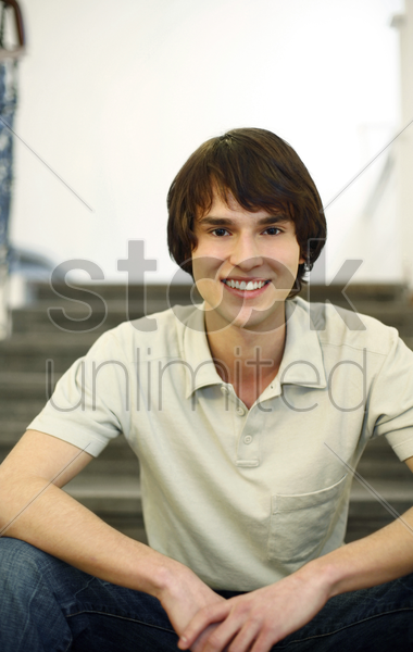 man sitting on the staircase smiling stock photo