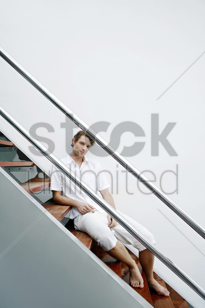 man sitting on the staircase stock photo