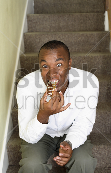 man sitting on the stairs eating bun stock photo