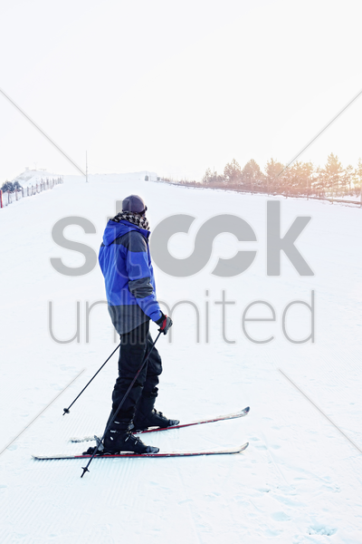 man skiing on winter day stock photo