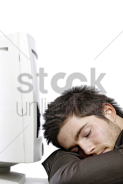 man sleeping in front of the computer screen stock photo