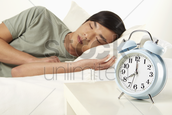 man sleeping on bed stock photo