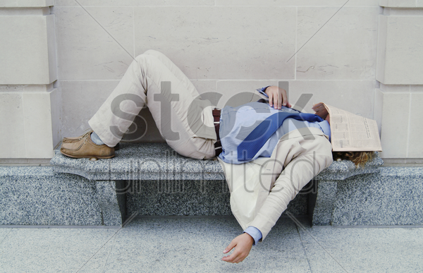 man sleeping on the bench with newspaper covering his face stock photo